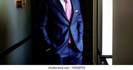 groom ready for wedding, blue suit and pink tie