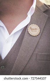 Groom round wooden badge boutonniere closeup of buttonhole on chest wedding details