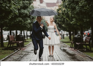 Groom runs away from bride with a black umbrella