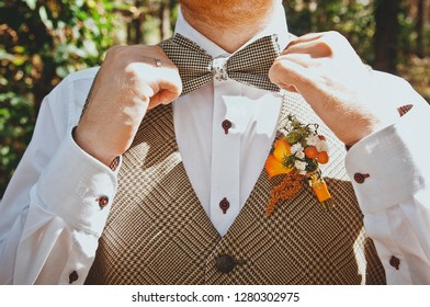 Groom in a shirt with a bow tie and a boutonniere. Flower design, floristry. Wedding day and accessories