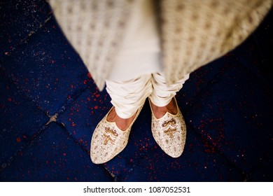 Groom showing wedding cream and gold Khussa shoes