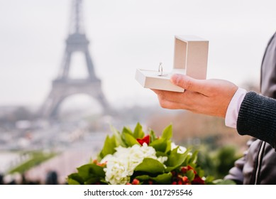 Groom shows proposal engagement ring under the Eiffel Tower in Paris, France.