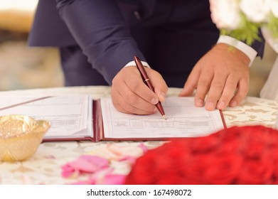 groom signing certificate in red folder