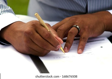 Groom signing marriage license or wedding contract. close-up