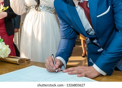 The groom signing registration of marriage certificate in Serbian civil registry office. Close up.