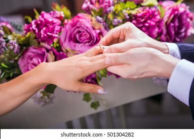Groom slipping ring on finger of bride at wedding