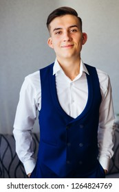 The groom smiles and holds her arms in his pants pockets. the groom in a white shirt, waistcoat and trousers