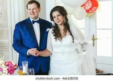 Groom in sparkling blue jacket holds hand of tender bride