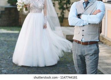 groom standing in street and waiting for bride