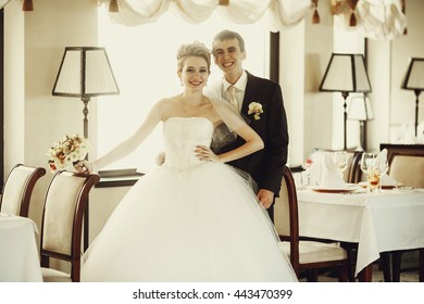Groom stands behind a pretty blonde bride holding his hand on her waist