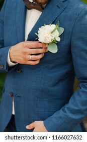 the groom straightens the buttonhole