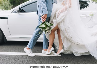 The groom in a striped suit and the bride in a white long dress stand holding hands in front of a white car on an asphalt road. City walk of the newlyweds along the markings.