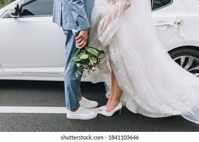 The groom in a striped suit and the bride in a white long dress are hugging against the background of a white car on an asphalt road with markings. City walk of the newlyweds.