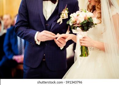 Groom in stylisch blauem Anzug setzt Hochzeitsring auf den Finger der Braut