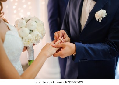 groom in a stylish suit puts on a gold wedding ring on the finger of a beautiful bride with a bouquet of peonies