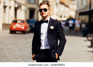 The groom in a stylish suit and sunglasses stands on the street on a beautiful sunny day.