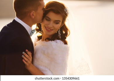 the groom in a suit kisses the bride in the head. bride with with a beautiful hairstyle. close up