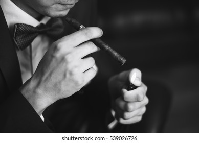 the groom in a suit smoking a cigar 1