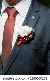 Groom in a suit with a tie and boutonniere. Flower design, floristry. Wedding day and accessories