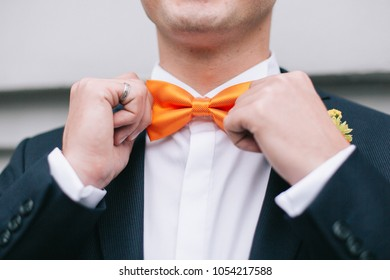 The groom in a suit touch up a bright orange bow tie. Special ocassion