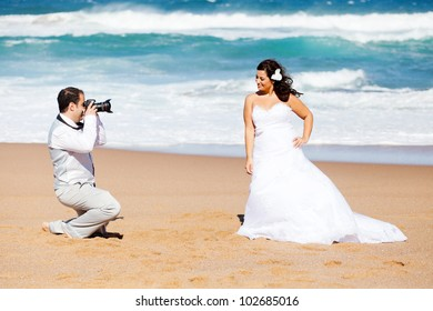 groom taking bride's photos on beach