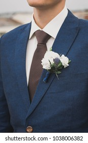 groom in a tie and with a buttonhole