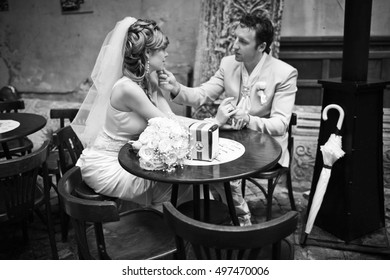 Groom touches bride's chin tender while they rest at little round table in the restaurant