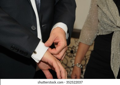 groom in tuxedo looking at his cufflinks while fixing them