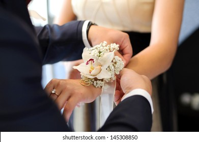 groom tying boutonniere to bridesmaid hand