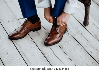 Groom tying shoelaces on boots