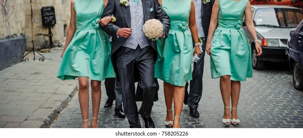 Groom walking with bridesmates with a bridal bouqet