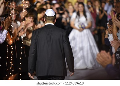 groom walking down the aisle to the bride at jewish wedding