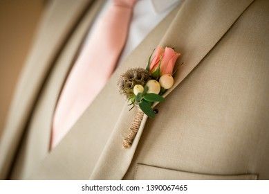 Groom wearing a suit with boutonniere pinned on the lapel in anticipation of his marriage celebration to his wife that he is in love with. Masculine combined with a feminine floral touch.