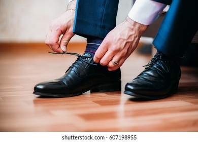 The groom wears black shoes, tying the laces