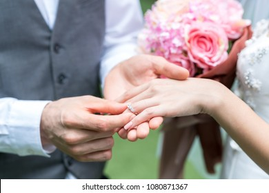 The groom wears the bride's ring.