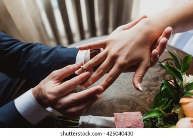 The groom wears the ring bride. Wedding ceremony. Ring of white and yellow gold