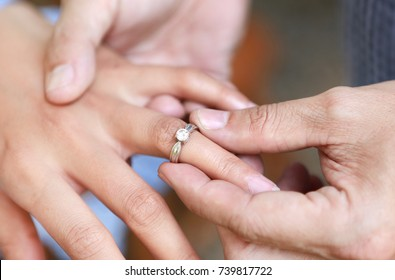 Groom wears ring on bride's finger. Selective focus at wedding ring.