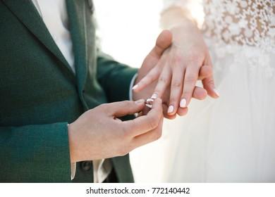 Groom wears ring on bride's finger. Wedding day.