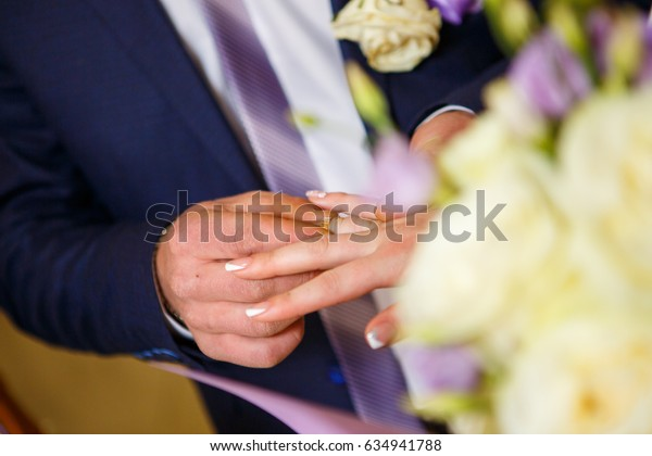 The groom wears a ring on the finger of a beautiful bride