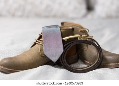 Groom wedding clothing shows a sense of vintage style with simple fashion from handmade leather items including a belt, shoes, and a nice grey tie.