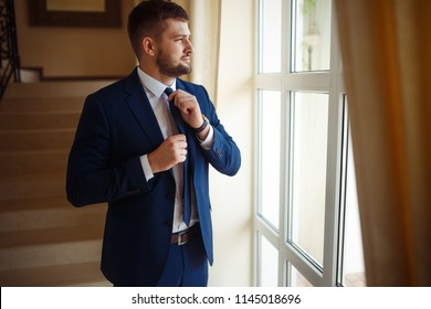 groom at wedding tuxedo smiling and waiting for bride in the hall of the hotel . Rich groom at wedding day. Elegant groom in costume and bow-tie. Groom in a suit holding buttonhole.