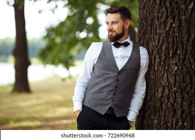 groom at wedding tuxedo smiling and waiting for bride. Rich groom at wedding day. Elegant groom in  costume and bow-tie. Groom in a suit holding buttonhole.