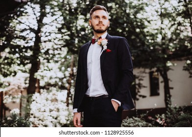 groom at wedding tuxedowaiting for bride. Rich groom at wedding day. Elegant groom in costume and bow-tie. Groom in a suit holding buttonhole.