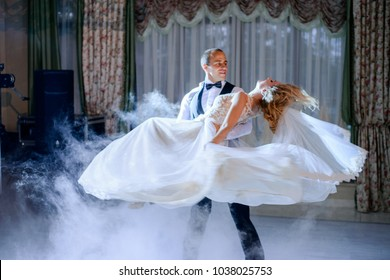 Groom whirls bride in the smoke dancing for the first time