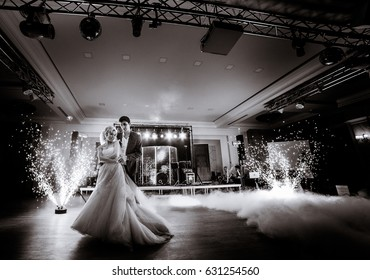 Groom whirls bride while smoke surrounds them on dancefloor