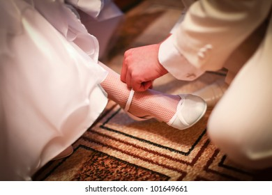 Groom in white costume is helping to wear classic wedding shoes on a bride before start of wedding ceremony.
