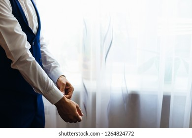 the groom in a white shirt, blue waistcoat and blue pants. standing by the window with white tulle