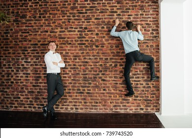 The groom in a white shirt is standing near a brick wall. His friend climbs up the wall. Funny photo.