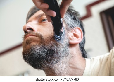 Grooming a beard trimmer. A nice gentleman in a beige T-shirt yourself shear his gray beard using a typewriter view from below