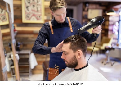 grooming, hairdressing and people concept - man and hairstylist or barber with fan drying hair at barbershop